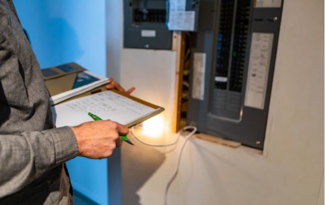 Electric inspector taking notes on paper while inspecting electric panel